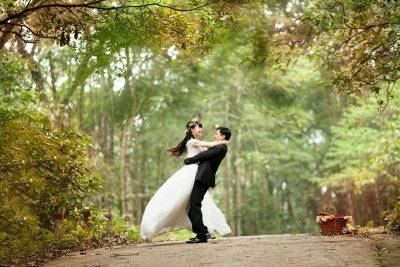 ウェデングドレスとタキシードを着た2人が森の中にいる