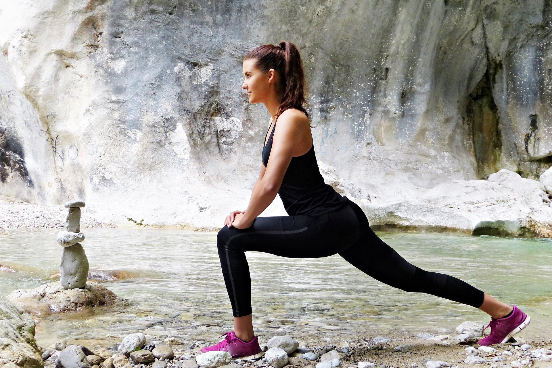 滝の前でストレッチをしている女性
