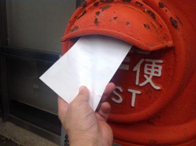 ポストで郵便物を出している