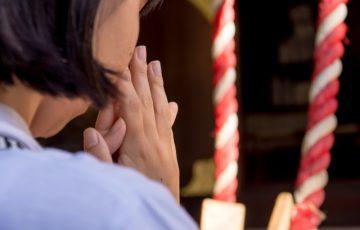 神社やお寺でお願いをする女性
