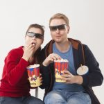 映画館でポップコーンを食べるカップル
