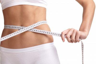 ダイエットでウエストを測っている女性